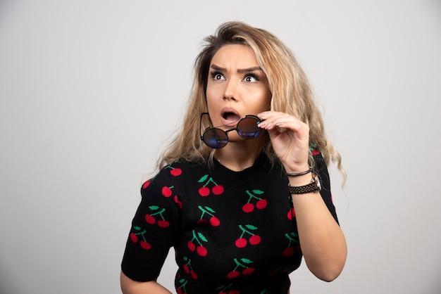 Jovem mulher com óculos, sentindo-se chocada na parede cinza.