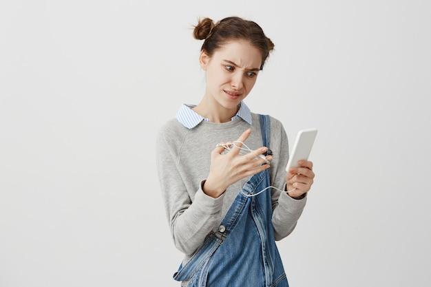 Jovem mulher com olhar de sobrancelhas franzidas, usando telefone celular não pode ouvir música por causa de desvendar fones de ouvido. menina na moda, tendo pouco problema com seus fones de ouvido. situação e solução
