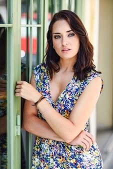 Jovem mulher com os olhos azuis que estão ao lado da porta bonita.