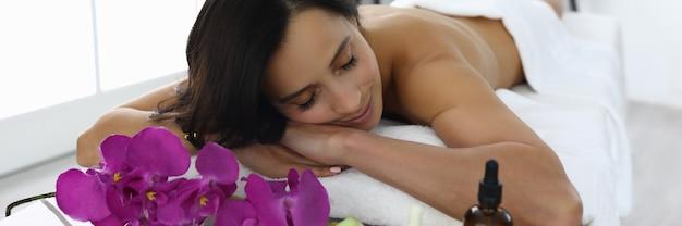 Jovem mulher com os olhos fechados encontra-se no sofá no salão de beleza. conceito de massagem de tratamentos de spa de beleza.