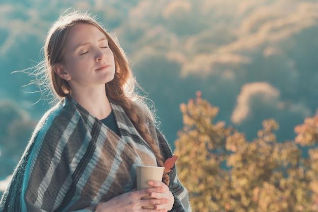 Jovem mulher com os olhos fechados gosta de ar. copo de papel nas mãos, dia de sol