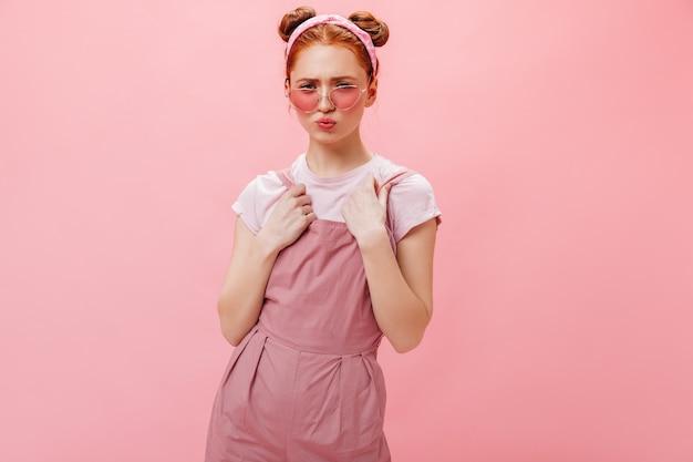 Jovem mulher com pães posando em fundo rosa. retrato de mulher de óculos elegantes, macacão rosa e blusa branca.