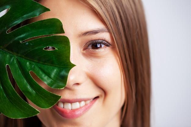 Jovem mulher com pele bonita, segurando uma folha verde