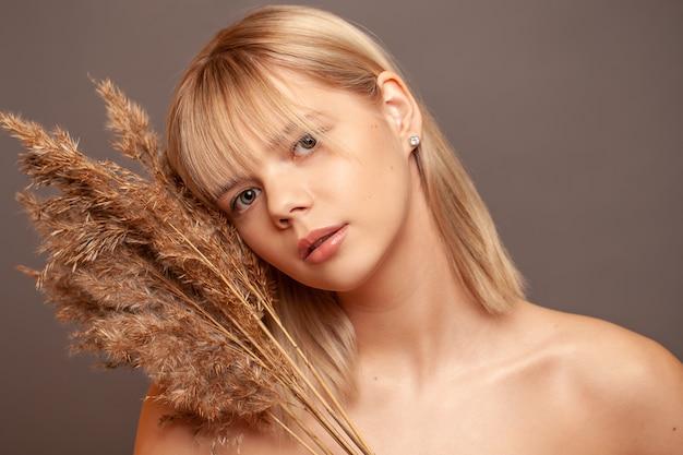 Jovem mulher com pele saudável fresca e cabelos segurando flores secas e sorrindo.