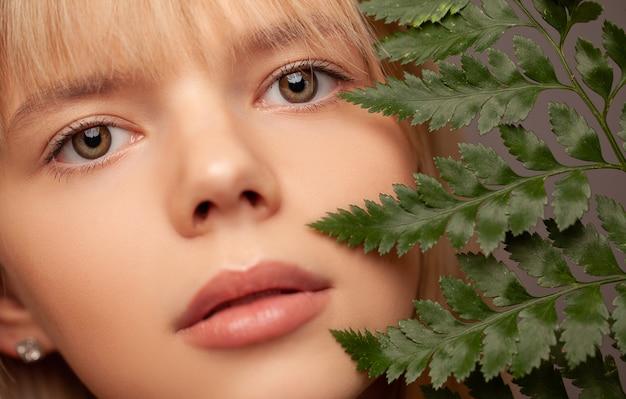 Jovem mulher com pele saudável fresca e cabelos segurando samambaia e sorrindo.