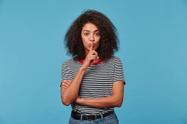 Jovem mulher com penteado afro, vestindo camiseta despojada sobre isolado
