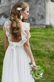 Jovem mulher com penteado de casamento em um vestido longo branco posando com um pequeno buquê em um campo verde, vista traseira.