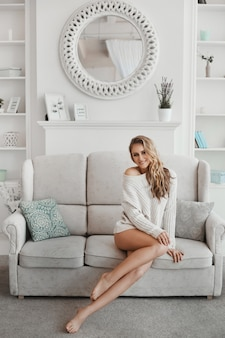 Jovem mulher com pernas muito sexy e cabelos loiros na camisola branca posando no sofá em um apartamento aconchegante de manhã