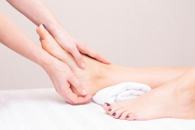 Jovem mulher com pés massagem no salão de beleza.