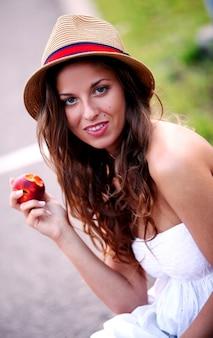 Jovem mulher com pêssego fresco na mão