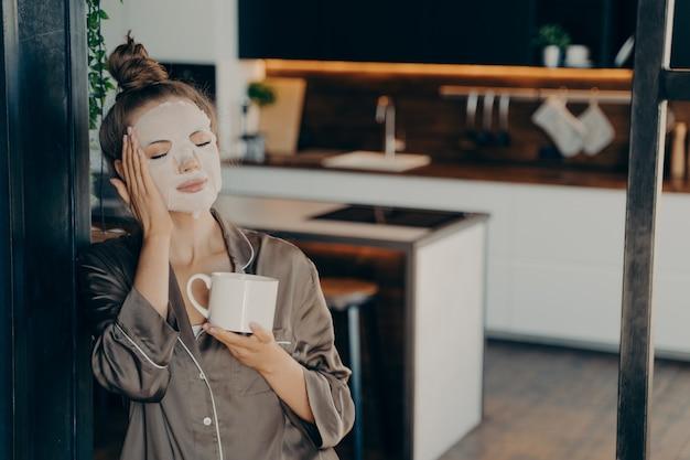 Jovem mulher com pijama de seda ficar em casa e desfrutar da xícara de café da manhã enquanto aplica a máscara descartável de cuidados da pele branca no rosto. procedimento de rotina diária para rejuvenescimento e cuidados com a pele