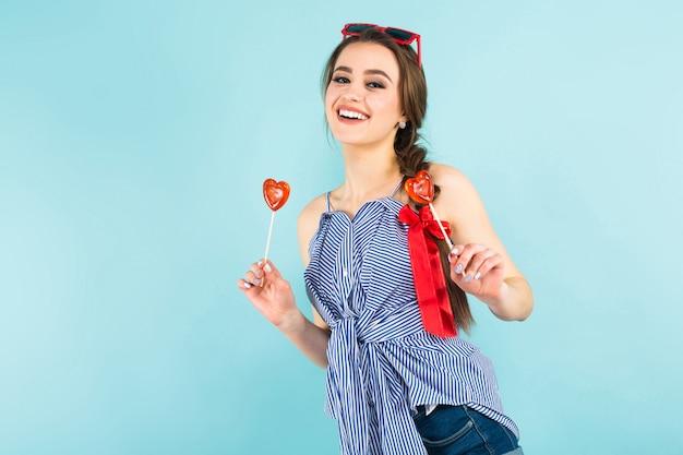 Jovem mulher com pirulitos em forma de coração
