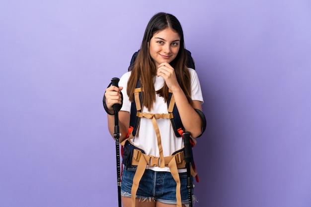 Jovem mulher com polos mochila e trekking isolados no pensamento roxo