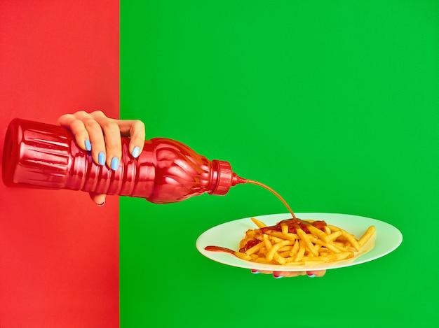 Jovem mulher com prato de batata frita com ketchup