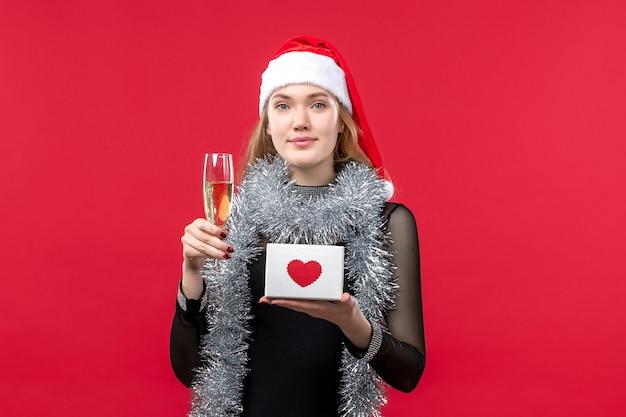 Jovem mulher com presente comemorando na mesa vermelha feriado cor de natal