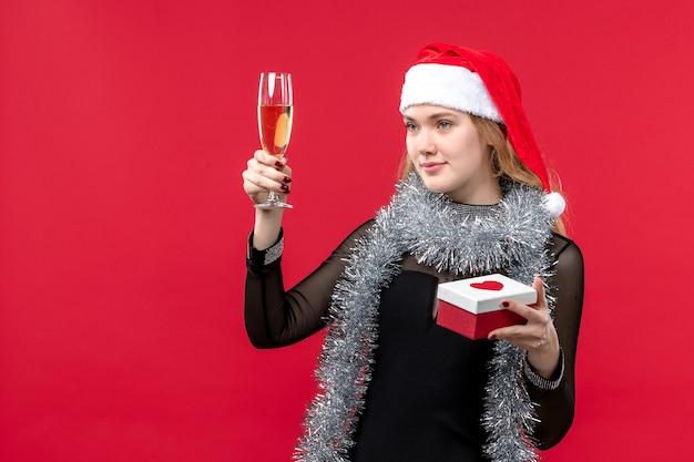 Jovem mulher com presente comemorando na mesa vermelha feriado cor natal