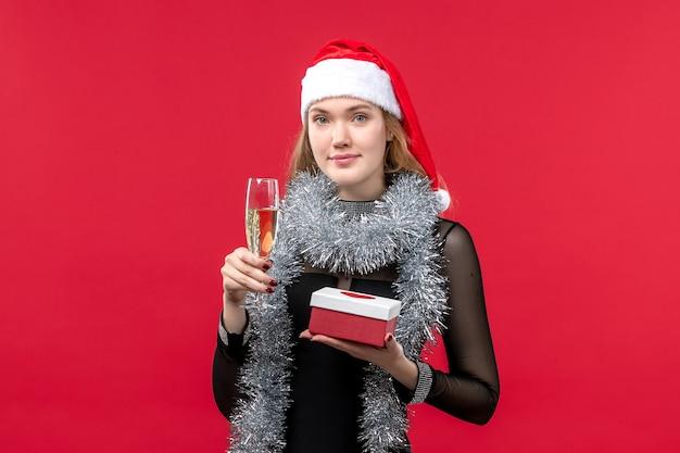 Jovem mulher com presente comemorando na parede vermelha feriado cor de natal