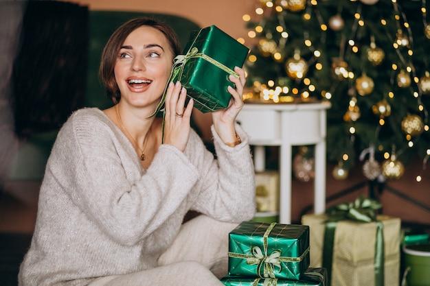 Jovem mulher com presente de natal pela árvore de natal