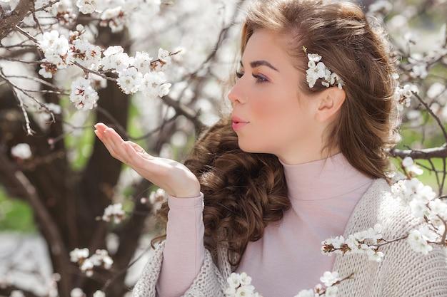 Jovem mulher com presente ou presente de primavera. senhora bonita no fundo natural da primavera ao ar livre no jardim.