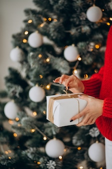 Jovem mulher com presentes de natal perto da árvore de natal