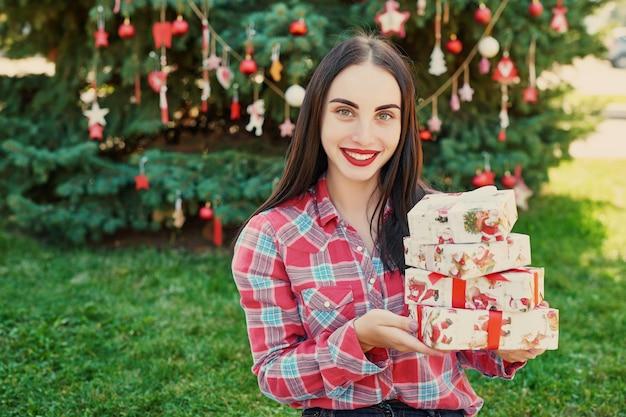 Jovem mulher com presentes perto de uma árvore de natal, natal em julho na natureza