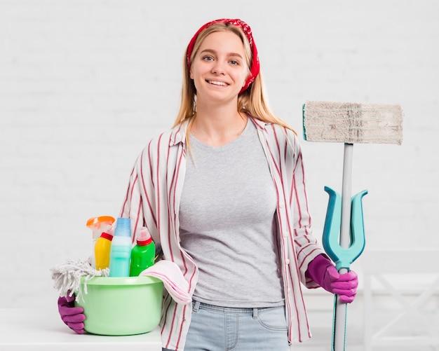 Jovem mulher com produtos de limpeza
