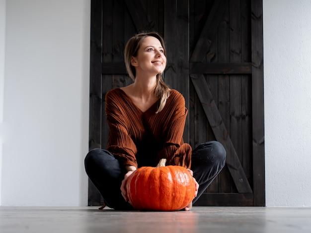 Jovem mulher com punkin sentado no chão