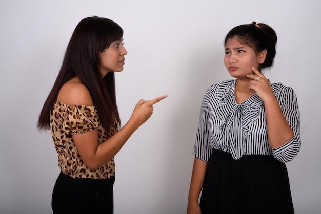 Jovem mulher com raiva apontando para uma jovem adolescente chorando