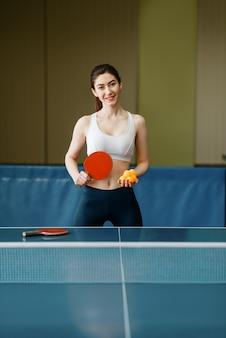 Jovem mulher com raquete de pingue-pongue e bola na mesa dentro de casa.