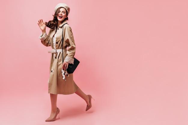 Jovem mulher com roupa bege de outono acenando com a mão e posando com um sorriso no fundo rosa.