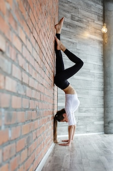 Jovem mulher com roupa esporte preto e branco se estende na parede no ginásio