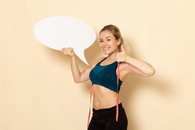 Jovem mulher com roupa esportiva segurando uma placa branca de frente