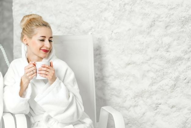 Jovem mulher com roupão de banho relaxante com uma xícara de chá na sala de sal. aplicação de terapia de sal no spa