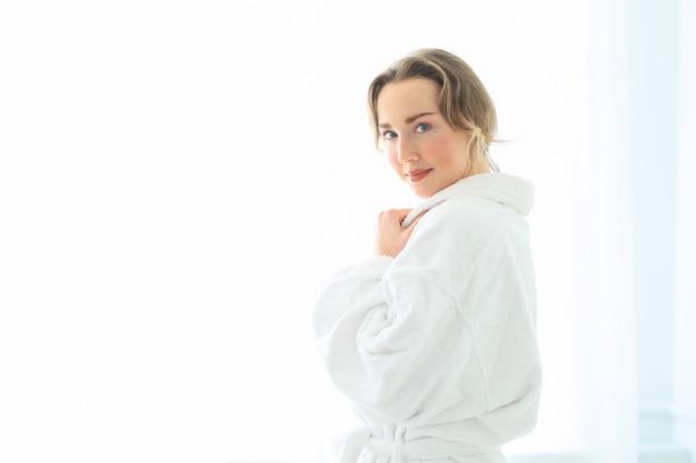 Jovem mulher com roupão depois do banho