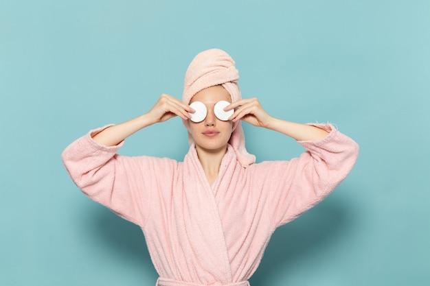Jovem mulher com roupão rosa após o banho, cobrindo os olhos no azul
