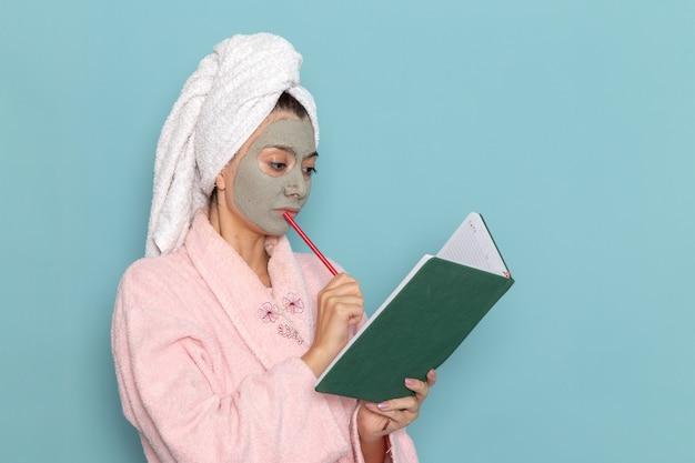 Jovem mulher com roupão rosa após o banho lendo caderno na parede azul beleza água creme autocuidado banheiro