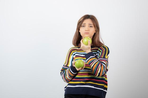 Jovem mulher com roupas casuais, em pé com maçãs verdes sobre fundo branco.