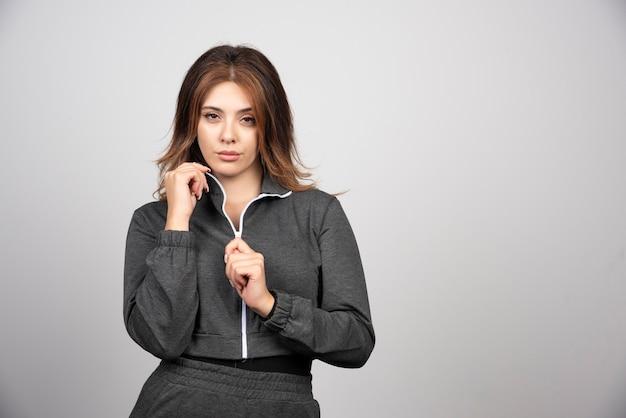 Jovem mulher com roupas casuais, em pé e posando.