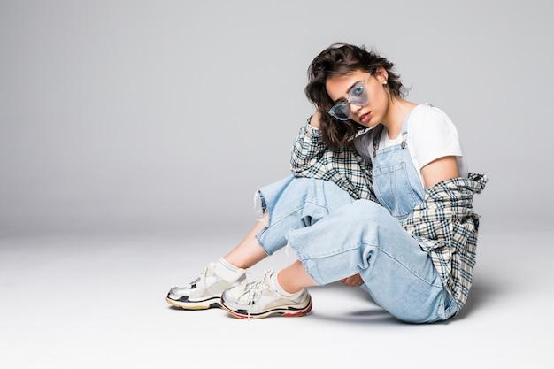 Jovem mulher com roupas casuais sentada no chão, posando sobre um espaço de cópia de parede cinza