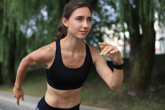 Jovem mulher com roupas esportivas, correndo durante o exercício ao ar livre.