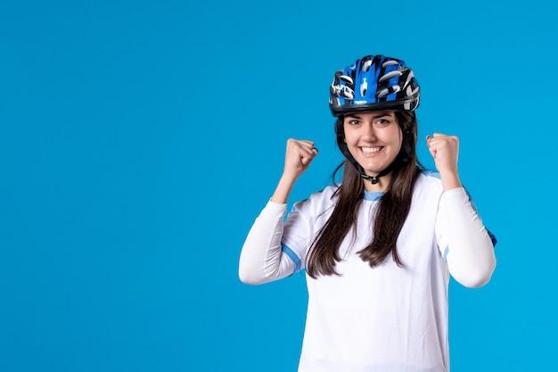 Jovem mulher com roupas esportivas e capacete na parede azul de frente