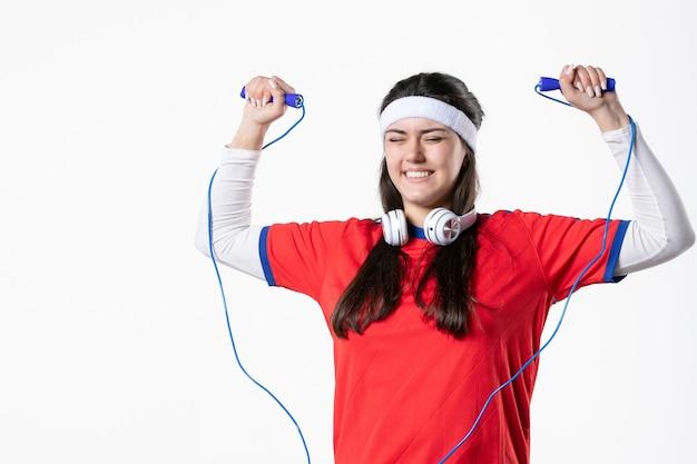 Jovem mulher com roupas esportivas e cordas para pular na parede branca de frente