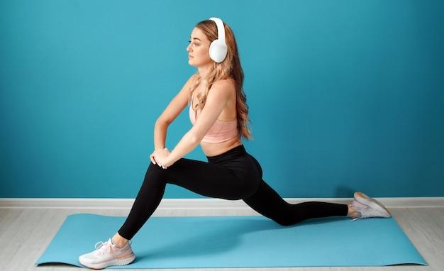 Jovem mulher com roupas esportivas e fones de ouvido, esticando os músculos das pernas sobre um fundo isolado