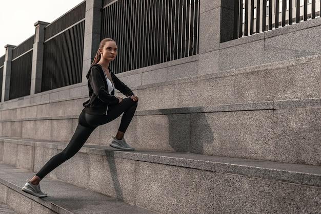 Jovem mulher com roupas esportivas está fazendo exercícios de aquecimento perto do estádio. pernas estendidas em escadas de pedra