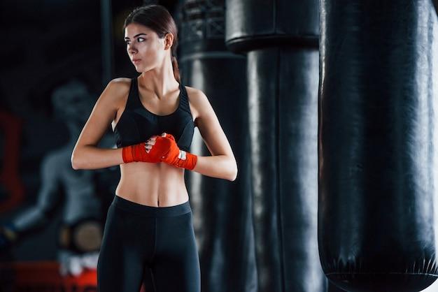Jovem mulher com roupas esportivas está no ginásio, tendo o dia de exercícios. concepção de boxe.