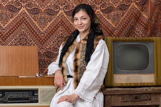 Jovem mulher com roupas nacionais em pé na sala com papel de parede vintage e interior com tv e rádio