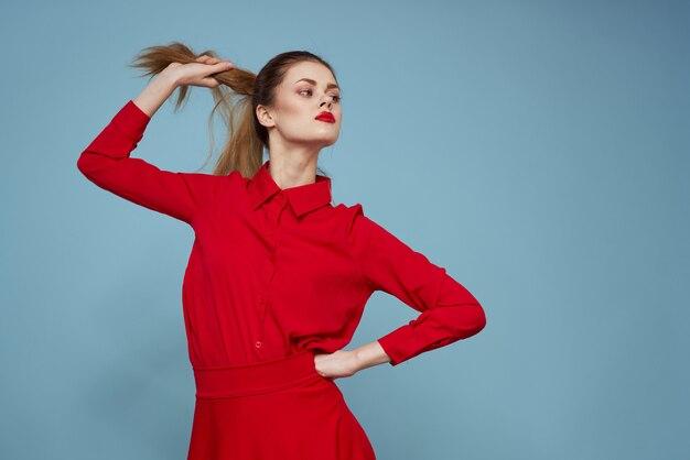 Jovem mulher com roupas vermelhas em uma parede azul luz emoções diferentes, moda elegante posando