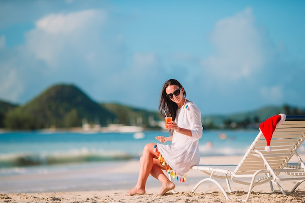 Jovem mulher com saboroso cocktail nas férias de verão