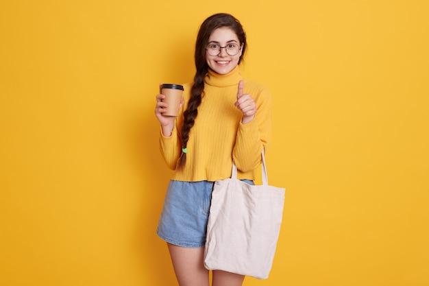 Jovem mulher com saco de algodão branco e xícara de café de papel nas mãos, olhando sorrindo e mostrando o polegar, vestindo blusa e jeans curtos.