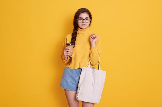 Jovem mulher com saco de algodão e xícara de café de papel nas mãos, posando contra a parede amarela, vestindo roupas elegantes e óculos redondos, mulher confiante indo às compras.